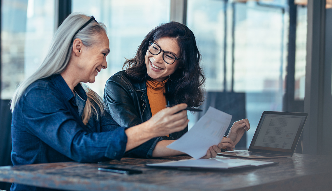 Smiling older business woman working together with a younger coworker at desk in high-rise office.