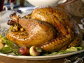 Stuffed turkey on table, woman serving green beans (USA)
