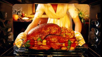 Familia latina cocinado el pavo para el Día de Acción de Gracias