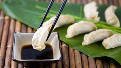 Chopsticks with Gyoza dumplings and soy sauce