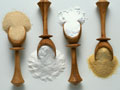 Four wooden spoons with various baking ingredients