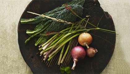 Algunas verduras como esparragos y cebollas en una tabla cde cortar