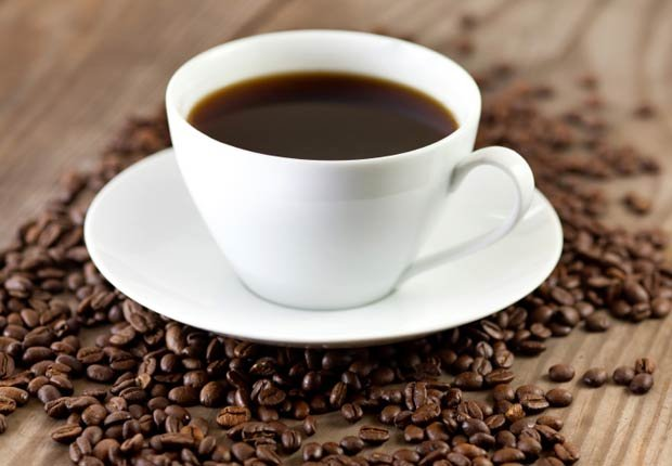 cup of black coffee surrounded by coffee beans
