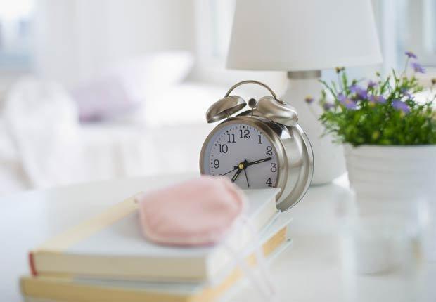 Libros, una máscara para el sueño y un despertador en la mesita de noche - Tácticas para bajar de peso rápido