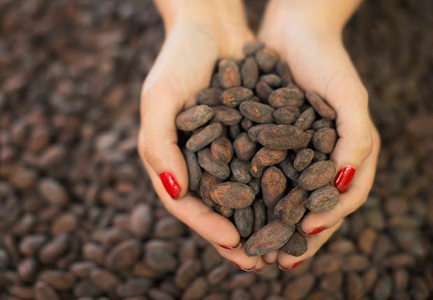 Mujer con unos granos de cacao en la mano, Beneficios para la salud de Cacao