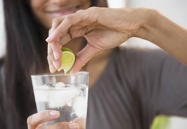 Mujer poniéndole limón a un vaso de agua, 10 buenas razones para agregar el limón a su dieta