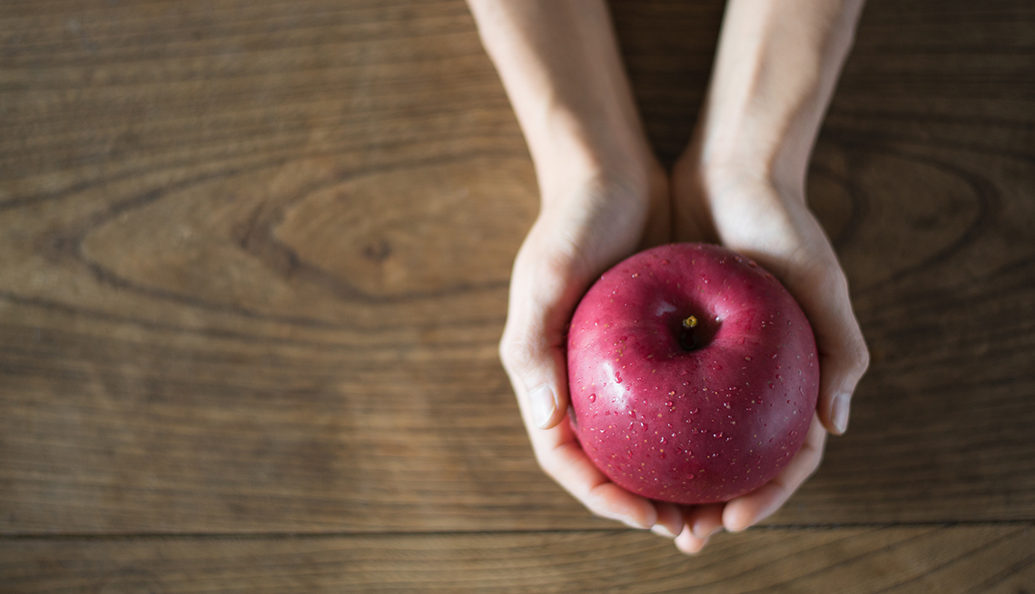 A woman holding an apple
