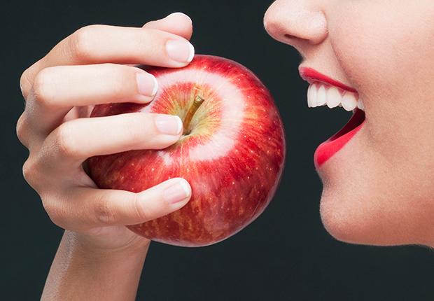 Mujer muerde una manzana roja