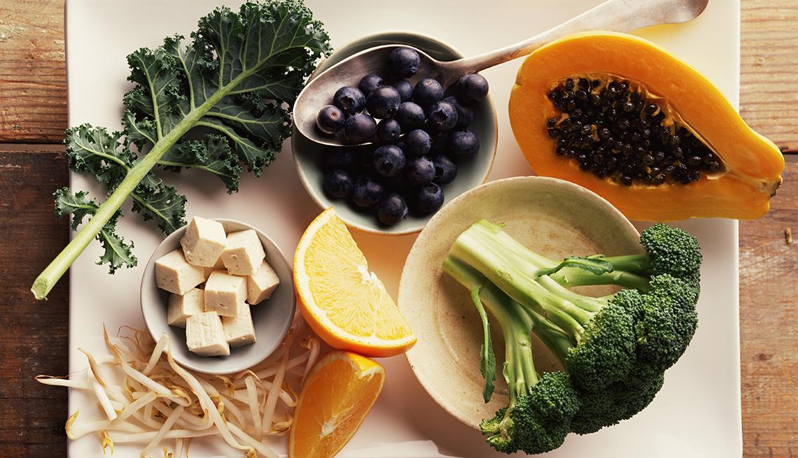 Col rizada, brócoli, papaya, naranja y arándano sobre la mesa