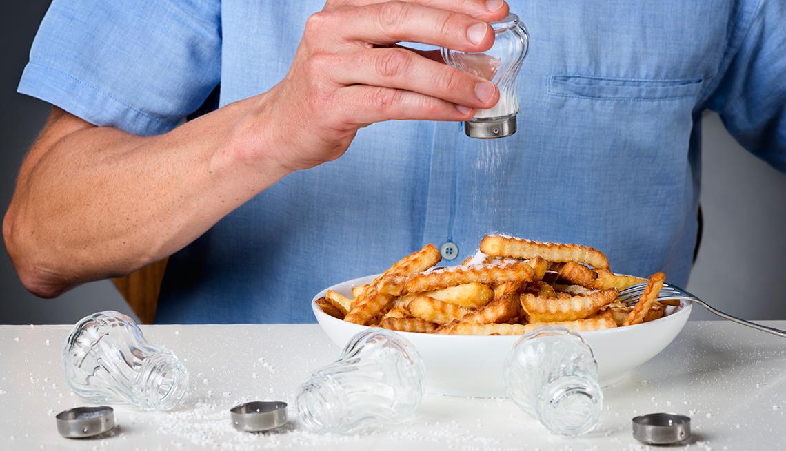 Persona poniéndole sal a sus papas fritas