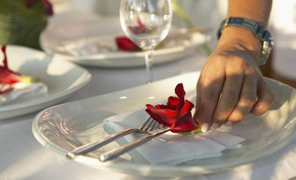 placing flower on dinner plate