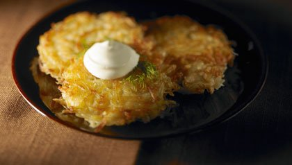 Three potato latkes with sour cream