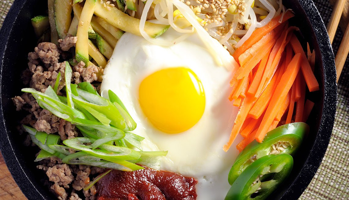 Overhead Shot Of A Bowl Of Bibimbap Which Features Rice, Egg, Vegetables And Minced Meat, AARP Food And Recipes, Authentic Asian Dishes