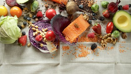 superfoods to eat for optimal health fish, vegetables, fruit and grain on linen