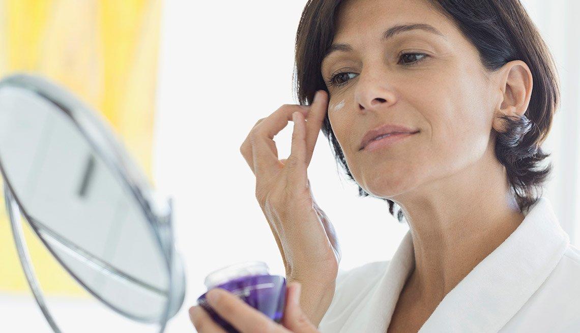 Mujer untándose crema en la cara
