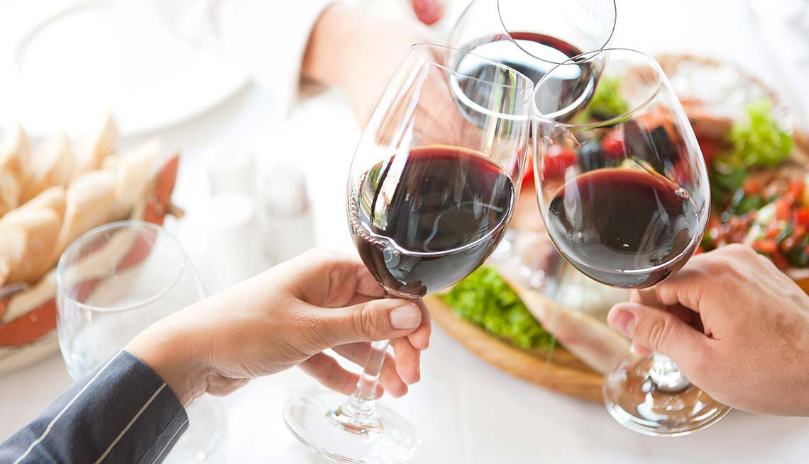 Dos personas brindan mientras toman vino