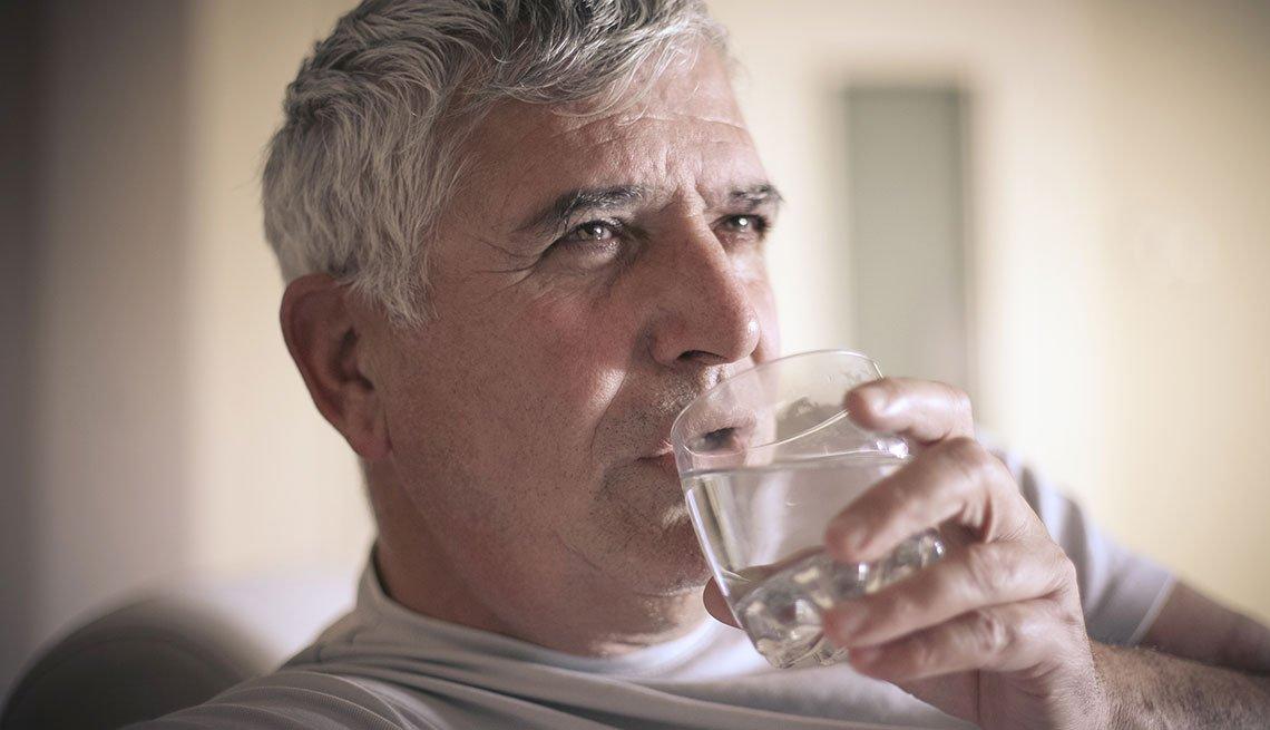 Un hombre toma agua de un vaso