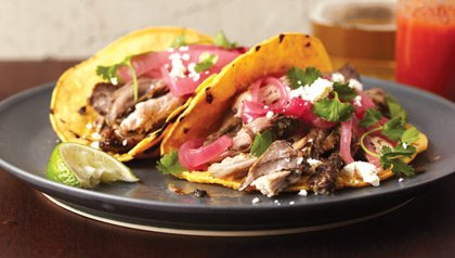 Pernil, a savory Puerto Rican pork roast served on tortillas.