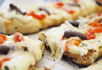 Grilled pizzas with ricotta, roasted peppers and olives.