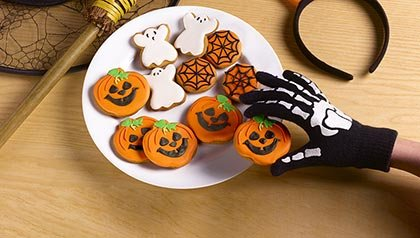 Hand wearing a skeleton glove reaches onto a plate of pumpkin and ghost shaped cookies as if stealing one from the batch, Homemade delights for Halloween