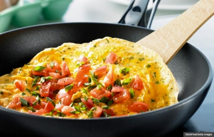 Omelette with pieces of tomato and chives in frying pan