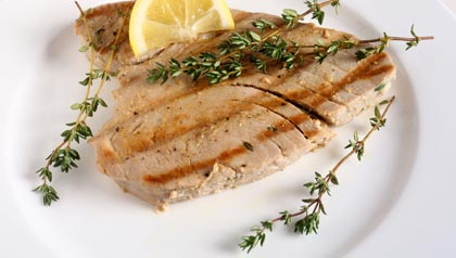 Grilled tuna steak with lemon wedge. (Art of Food/Alamy)