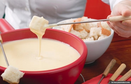 Woman eating cheese fondue, Unique Cookstr Fondue Recipes (the food passionates/Corbis)