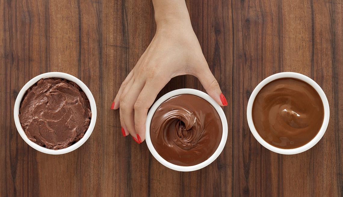 Mano de una mujer alcanza un pudín de chocolate