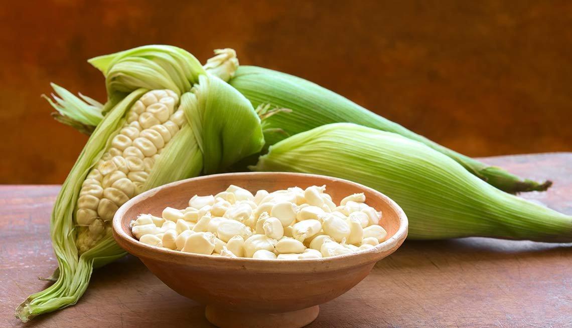 Plato con granos de maíz blanco y maíz enteros envueltos en hoja