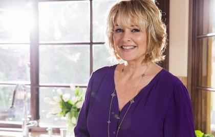 Christina Ferrare smiling at her kitchen