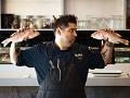 Chef Carlos Brescia sostiene dos pescados en la cocina