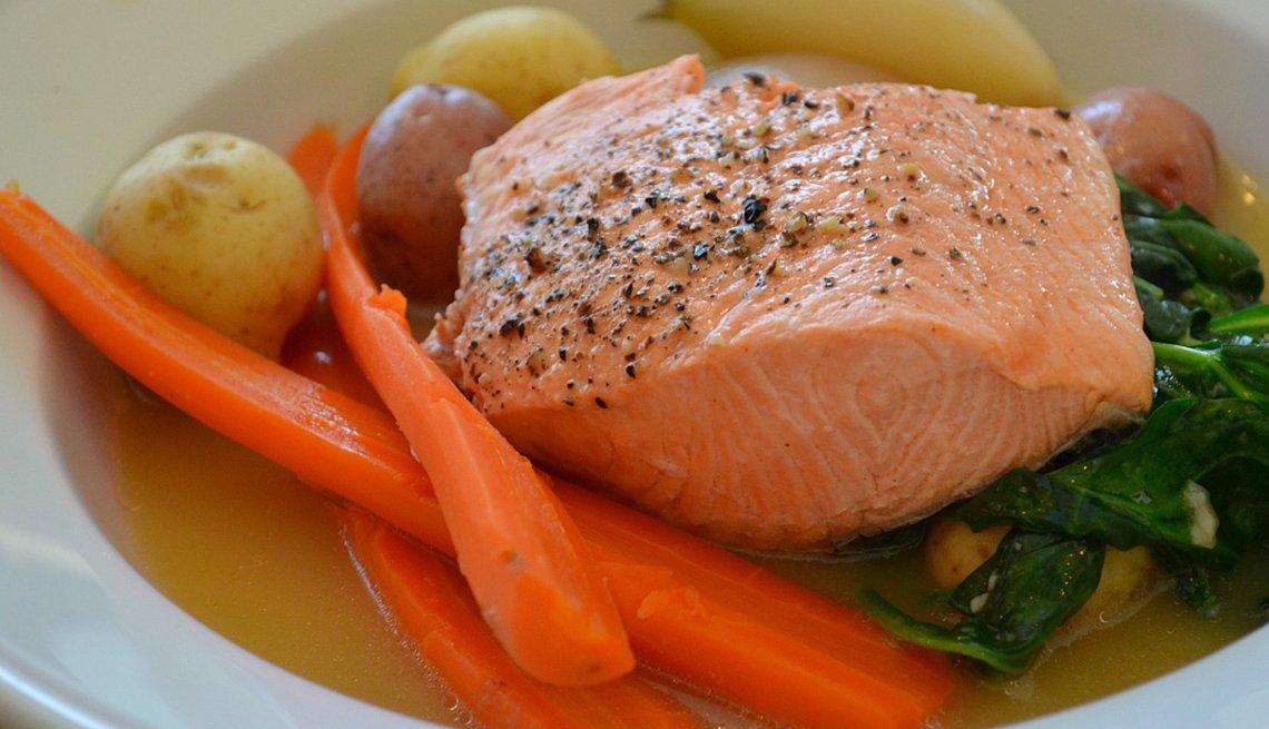 Salmón cocido servido en un plato con vegetales