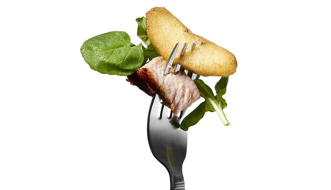 Tenedor con manzana y trozo de cerdo