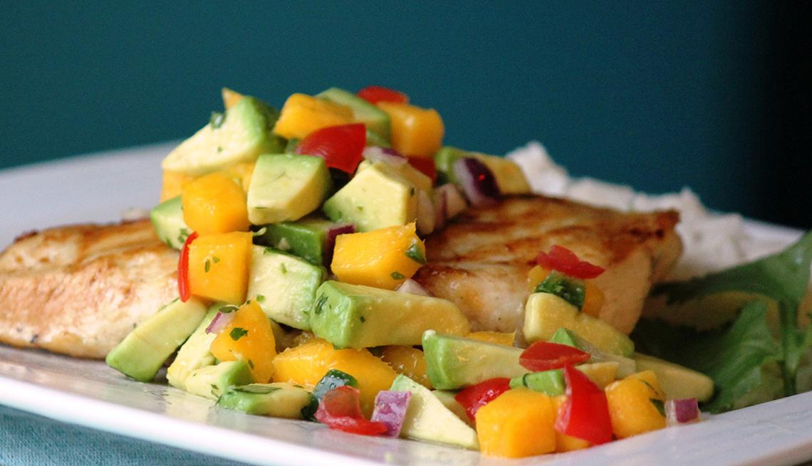 Trozo de pescado con salsa de mango y aguacate en la parte superior