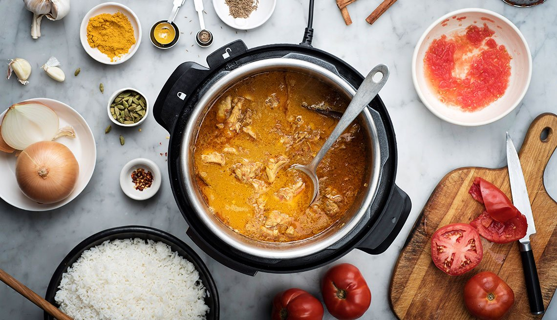 Coconut curry chicken is prepared in an Instant Pot cooker.