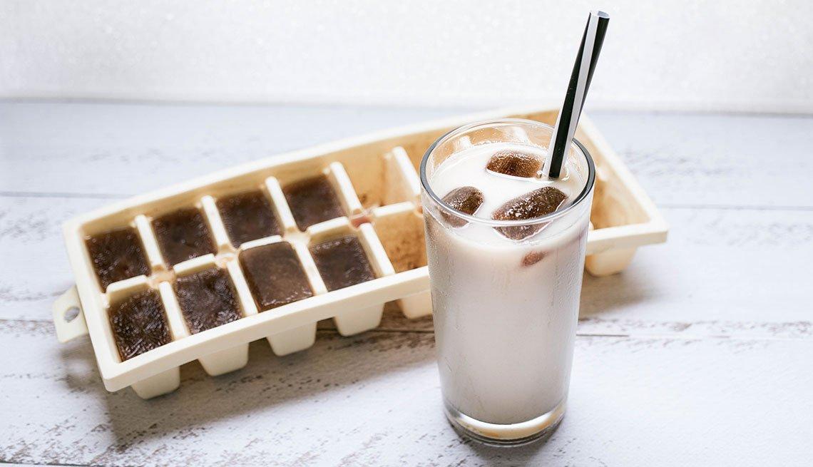 Cubetas de hielo con café y vaso de leche