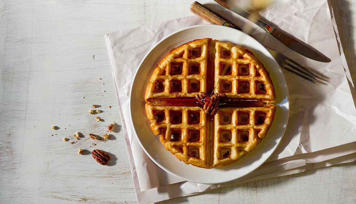 Waffle en un plato con jarabe y pacanas