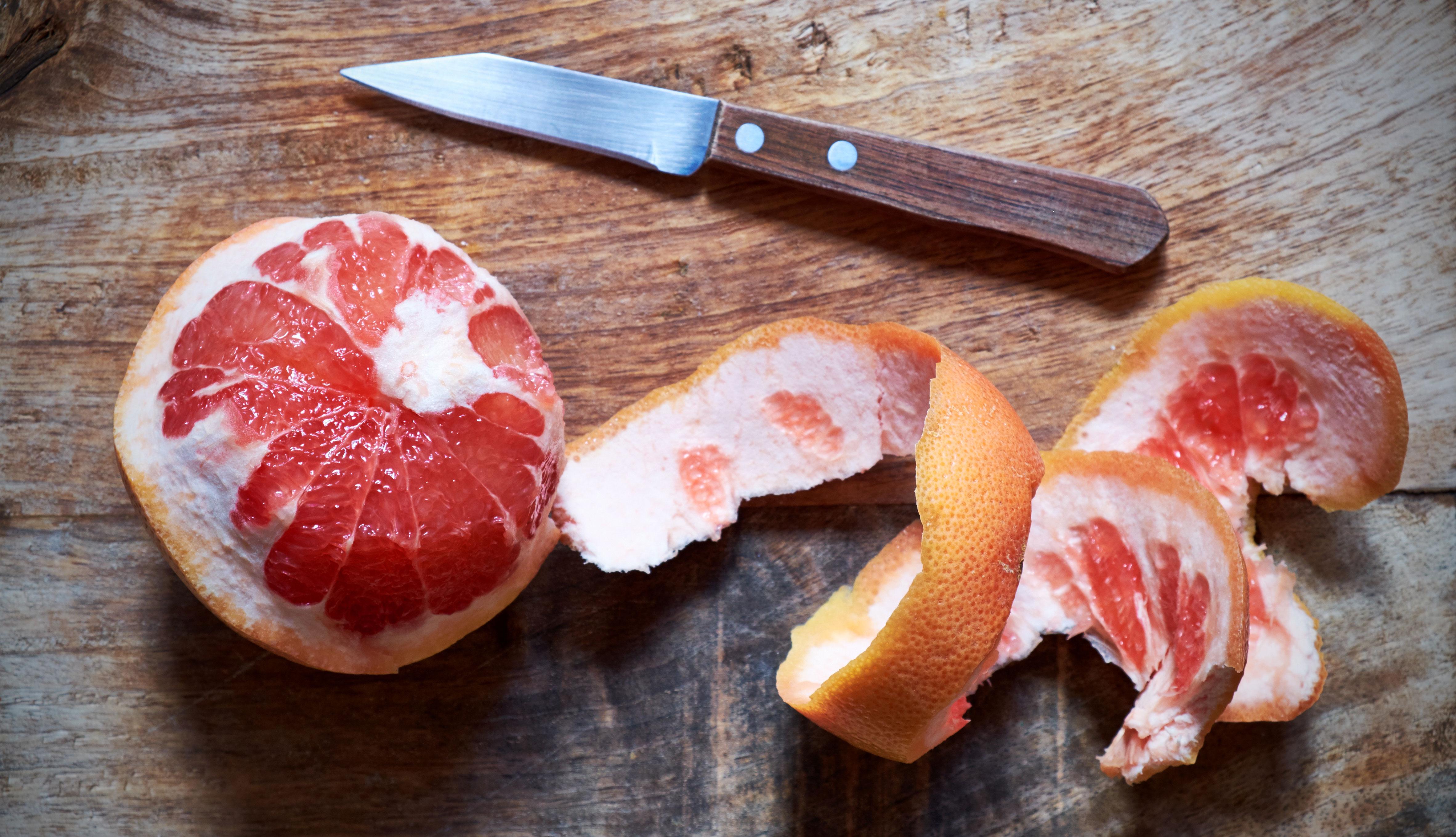 Toronja a medio mondar y un cuchillo sobre una mesa