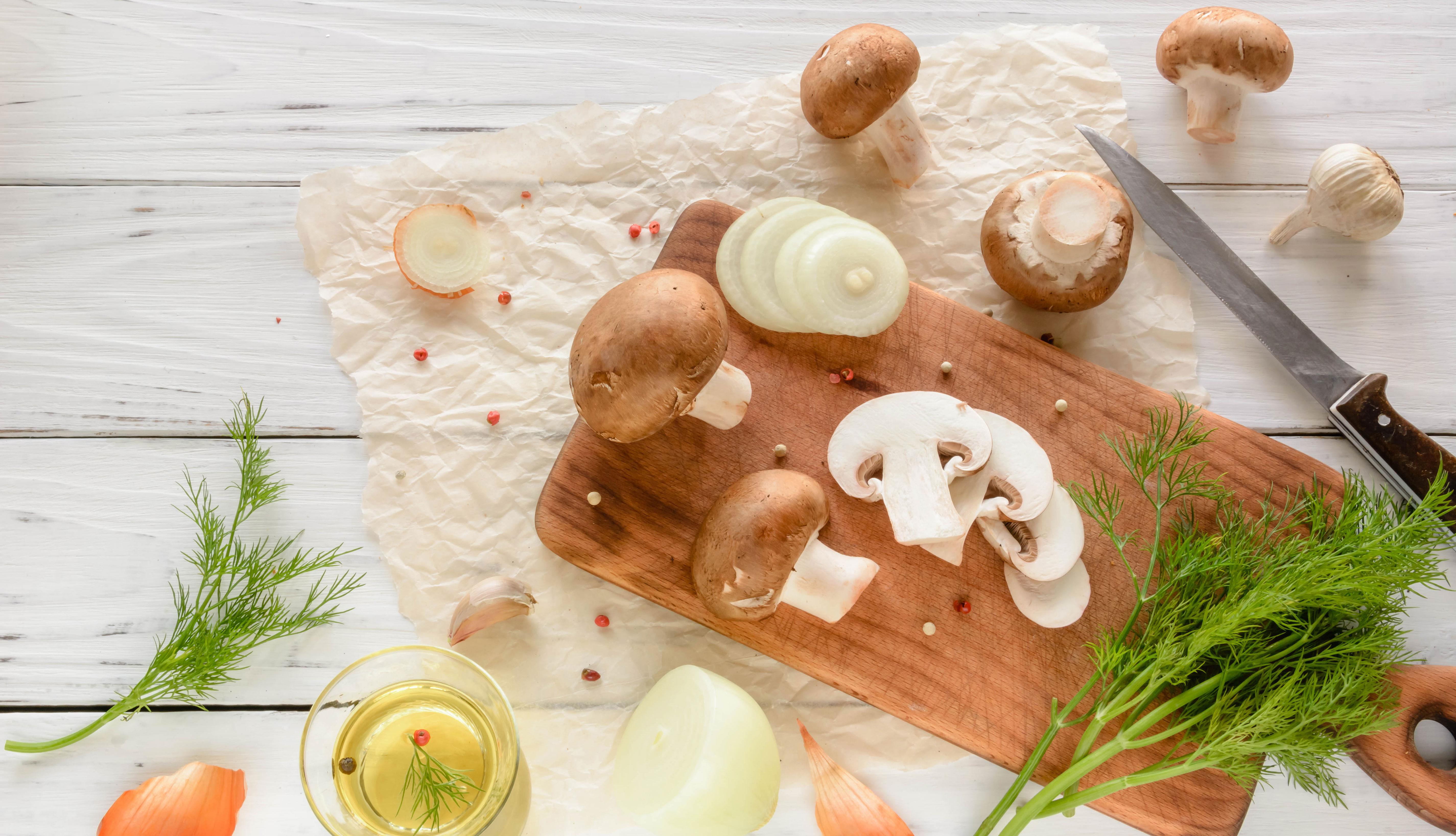 Hongos portobello y cebollas sobre un picador