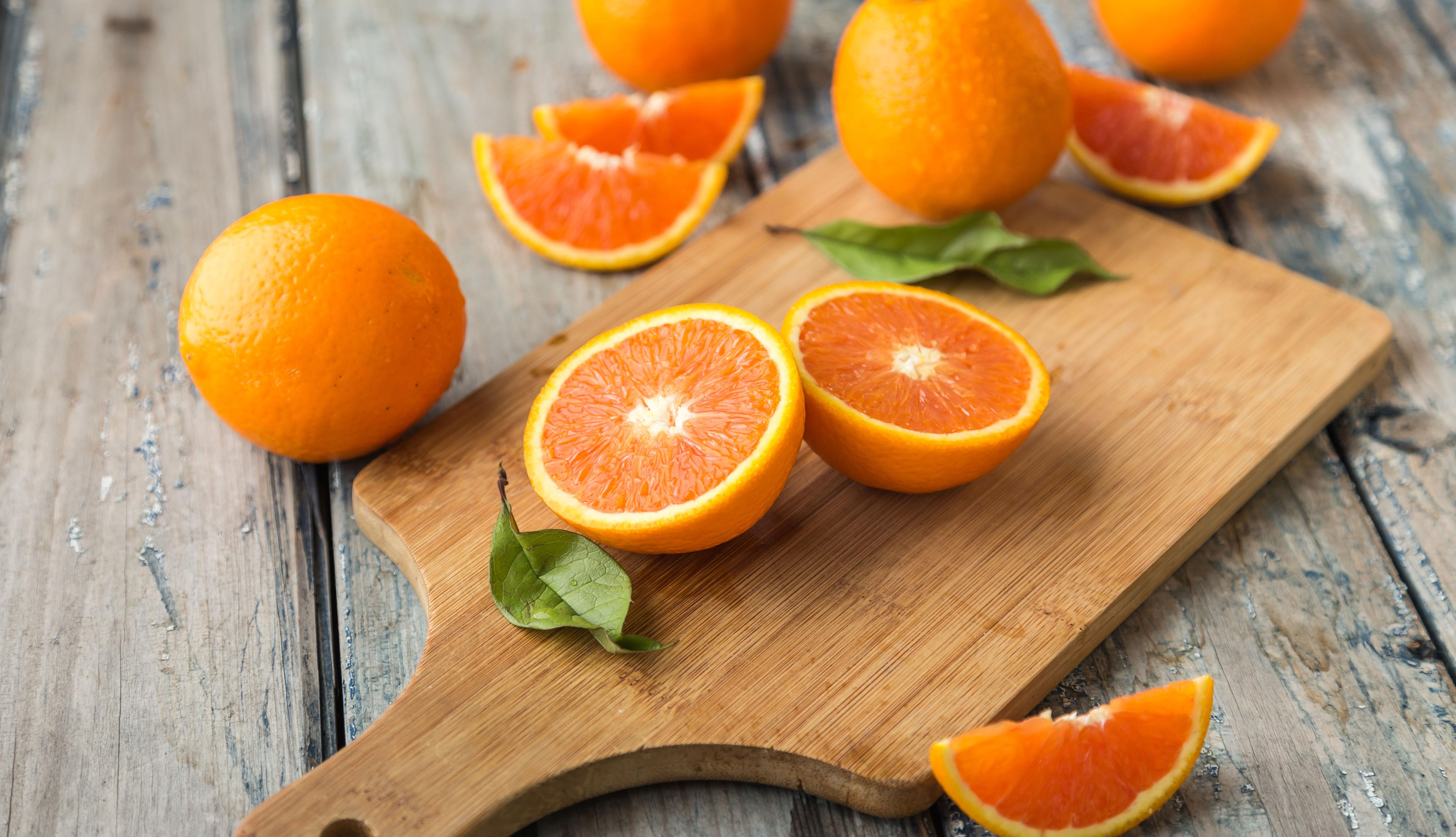 Naranjas cortadas y enteras sobre un picador