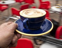 Cappucino being served at outdoor cafe.
