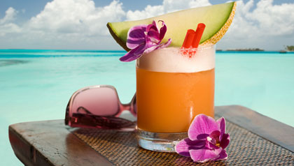 Fruity cocktail and sunglasses on a table on the beach.