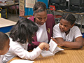 Two children read to adult, AARP Experience Corps