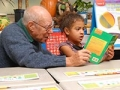 An elderly man reads to a child, AARP Experience Corps