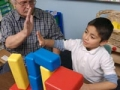Man playing blocks with boy, AARP Experience Corps, News Release