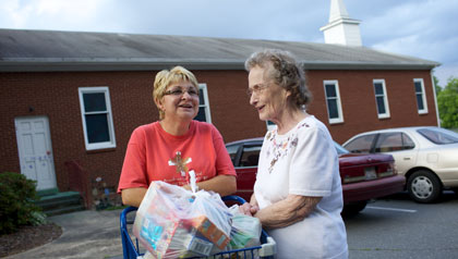 Two women share a laugh outside a food bank that AARP helps to stock.