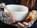 hands holding bread and a bowl of soup