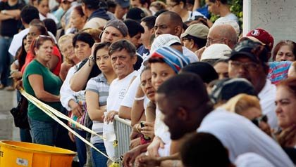 Miles de personas hacen fila para la entrega de alimentos en la Cámara de Comercio Latina evento el 16 de diciembre de 2009 en Miami, Florida