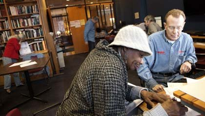 AARP New York tax-Aide woman and man work on taxes in library