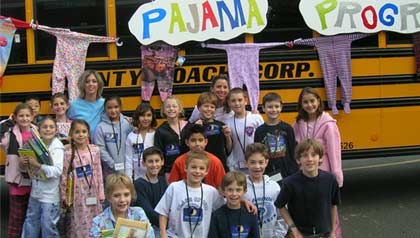 Volunteers pose before school bus donated by David Kucera for the Stuff a Bus drive which collects pajamas for children in group homes and local shelters